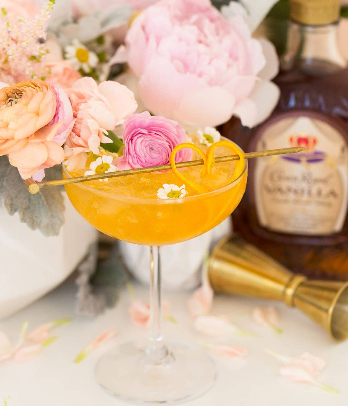 An orange cocktail drink with roses and orange peel.
