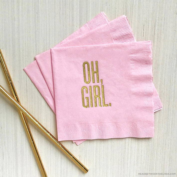 A set of pink napkins with the words Oh, Girl in gold printed on front.