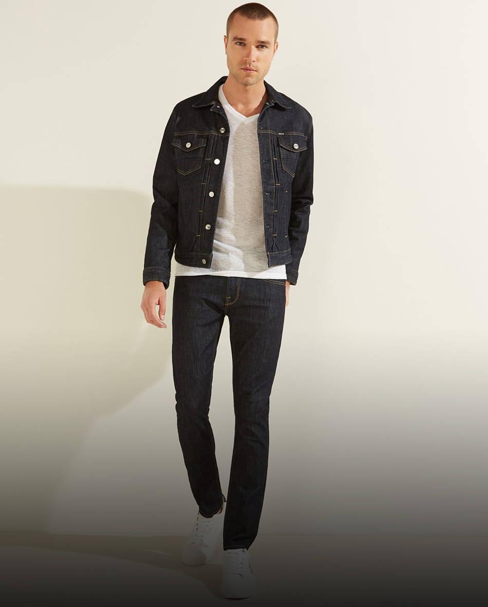 a man wearing dark blue GUESS denim jeans, a white GUESS shirt and a dark blue GUESS denim jacket