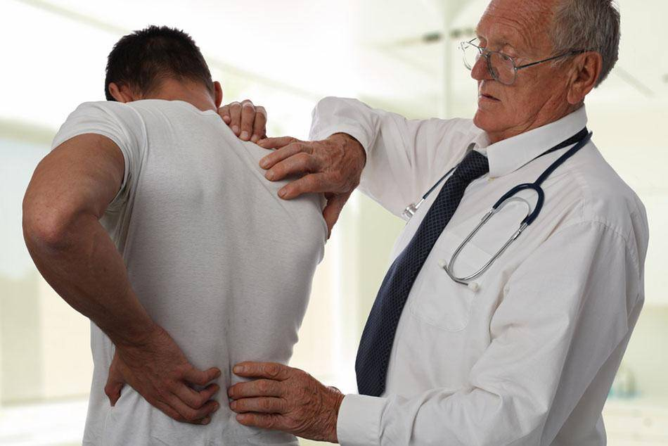 doctor checking man back pain