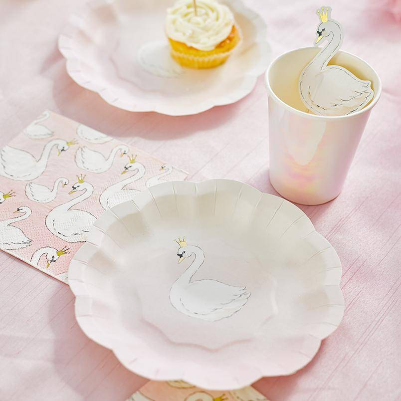 A photo of a table laid out with items from the  We Heart Swans baby shower ranges showcasing a paper plate with a swan design, pale pink party cup and napkins all on a pink tablecloth.