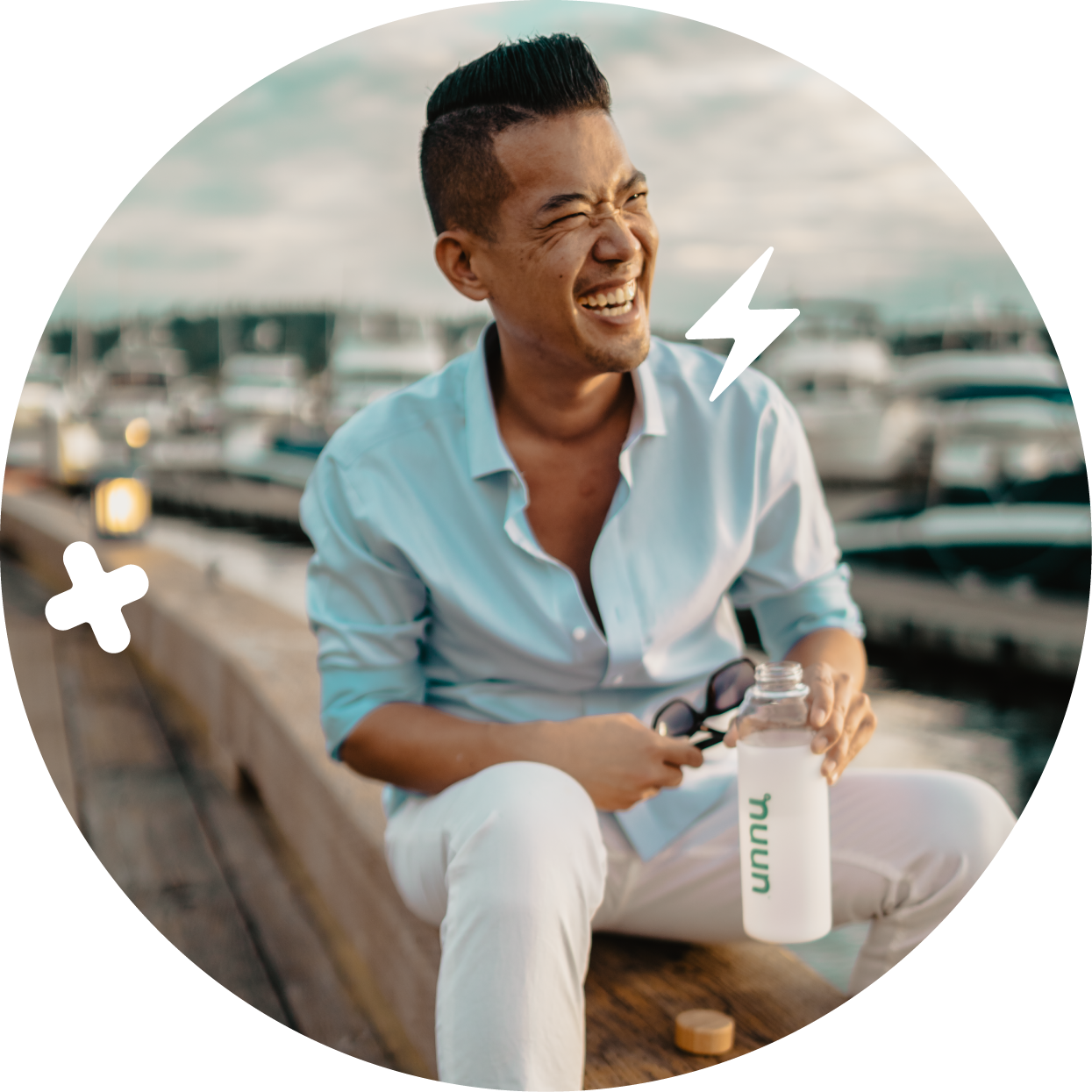 Man sitting on a dock laughing and holding a water bottle