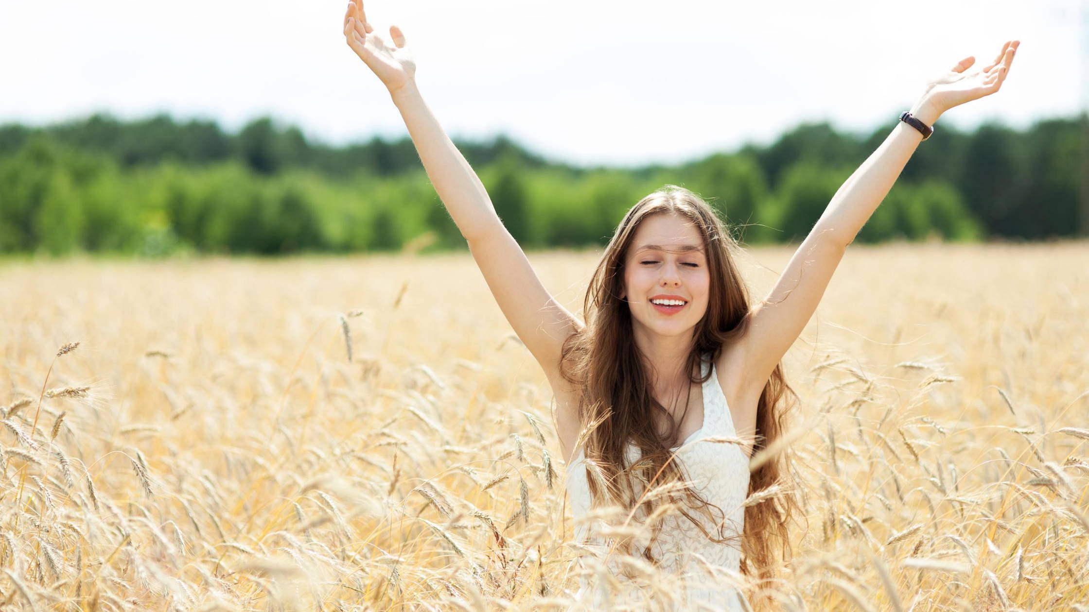woman in field raising arms up