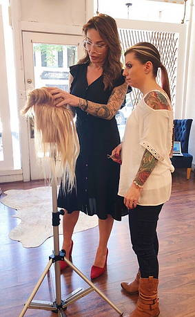 Christina Jones training a student on hair extension mastery within her in person classes