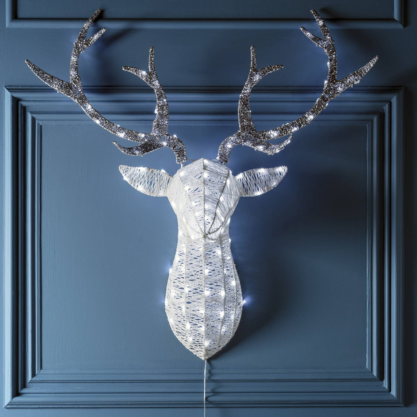 Glitter stag head silhouette Christmas light entwined with white LED hanging in a dining room