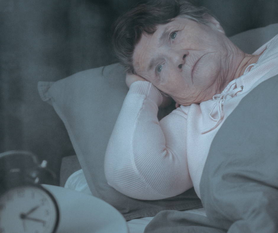 Elderly woman lying awake in her bed.