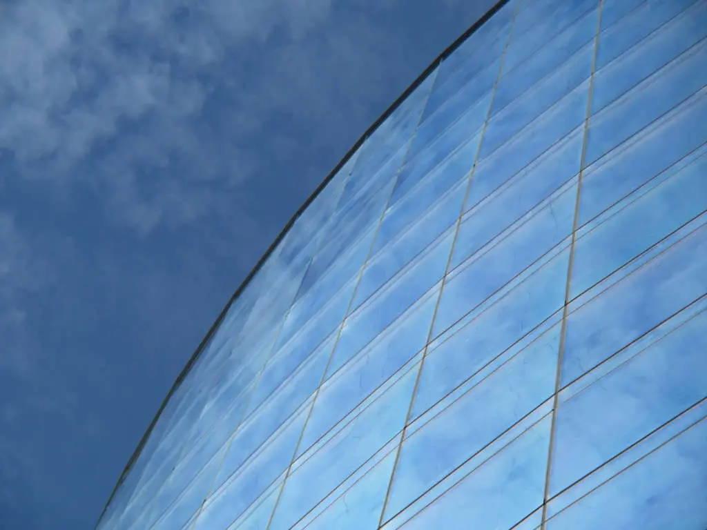 Immeuble de haute taille tout en verre et avec le ciel bleu se refétant dans les vitres