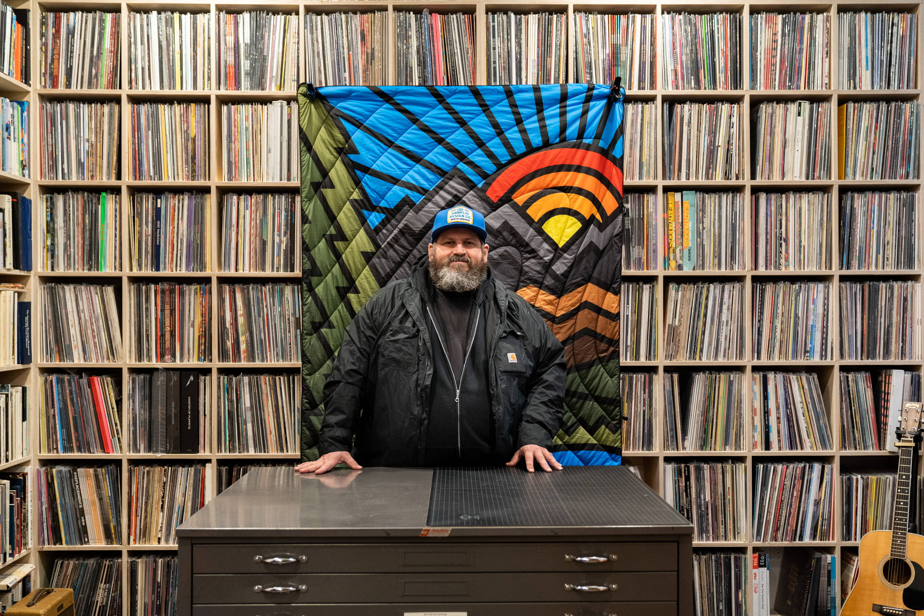 Rumpl Artist Division Aaron Draplin inside his Portland studio behind a wall of records and his blanket