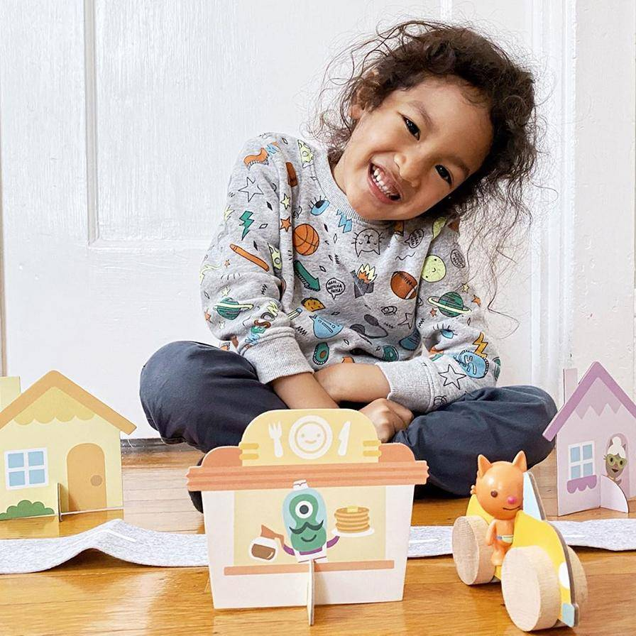 Child smiling with a Box playset