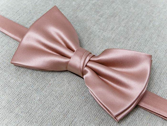 Mauve bow tie on a gray background