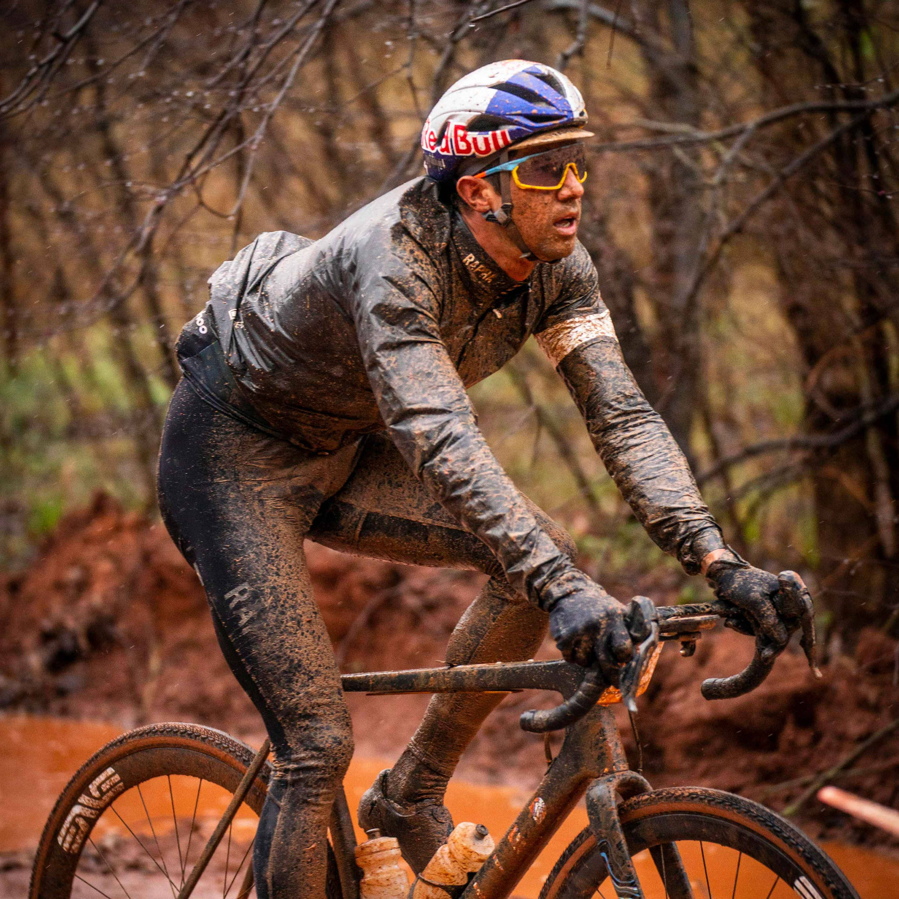Colin Strickland riding his bike covered in mud