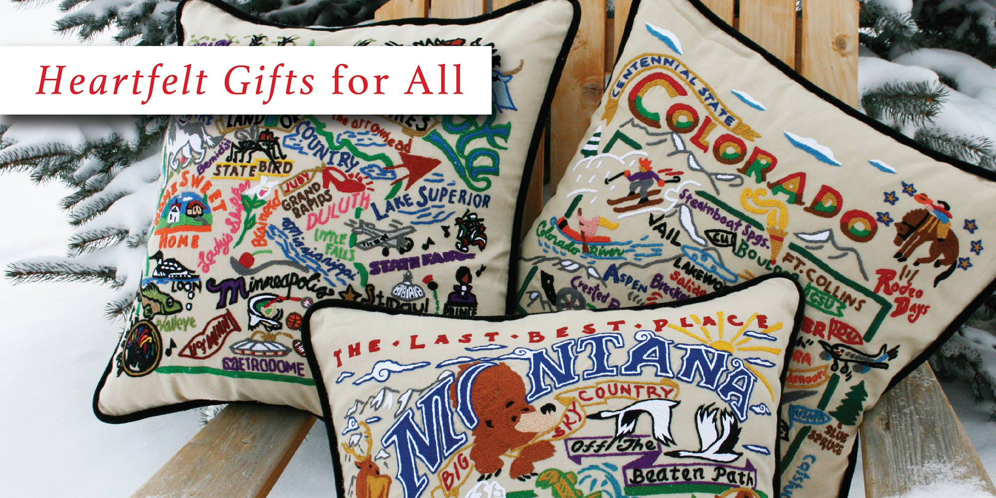 Minnesota, Colorado, and Montana hand-embroidered pillows in an adirondack chair in the snow