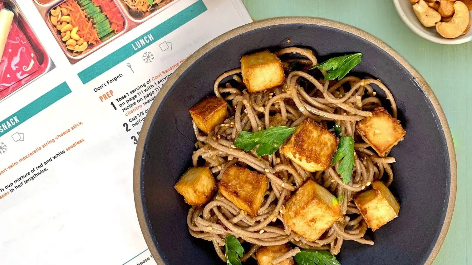 Cool sesame noodles in a gray bowl with baked tofu cubes and mint