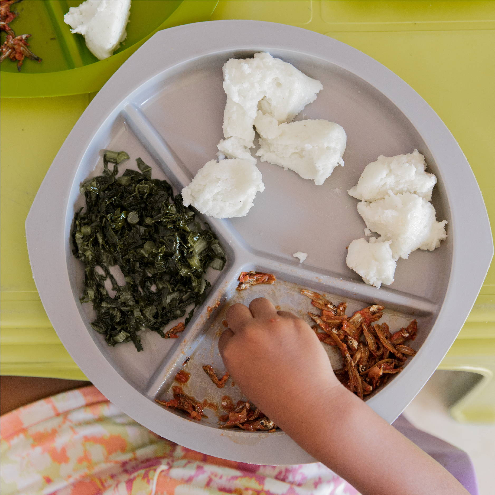 A small hand reaches onto a typical plate of food in Zambia: Nshima, buka buka fish, and greens.