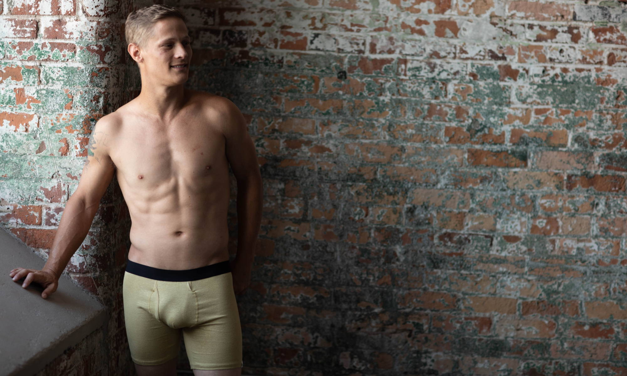 A man stands in front of a brick wall next to a window wearing WAMA hemp underwear in natural hemp color.
