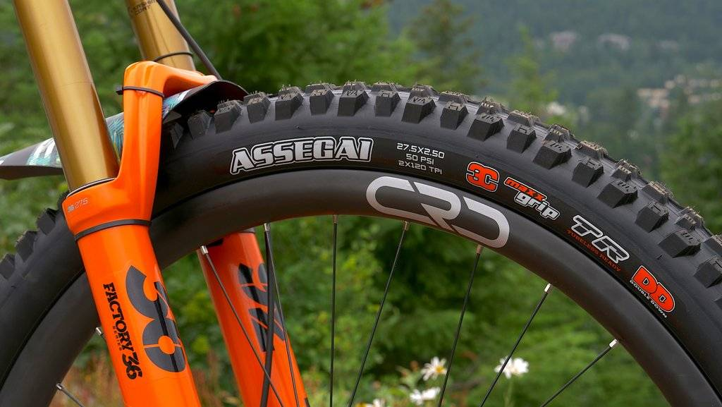 maxxis assegai mountain bike tire review detail of side knobs on a shiny orange fox factory 36