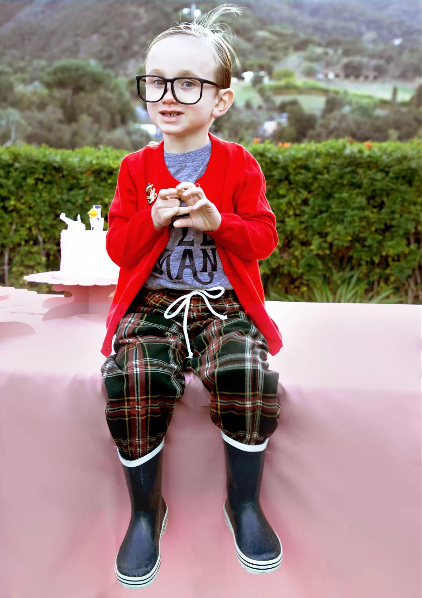 child sitting down wearing rain boots