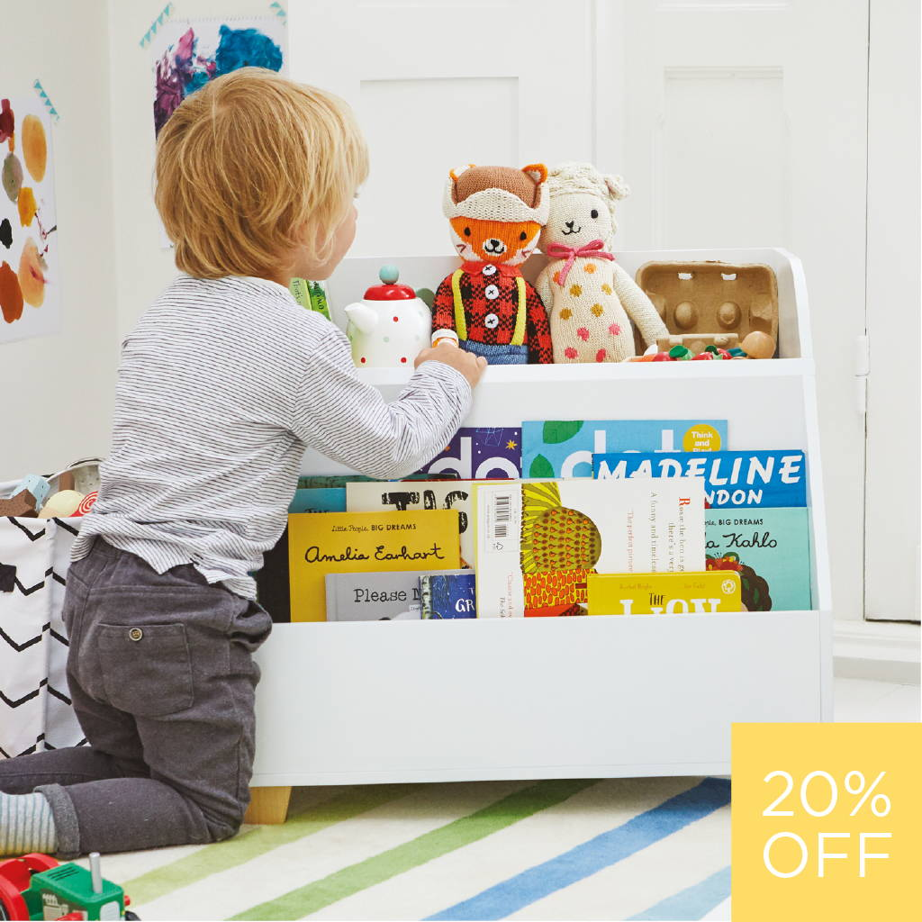Boy sitting next to white wooden book storage unit filled with books and toys.