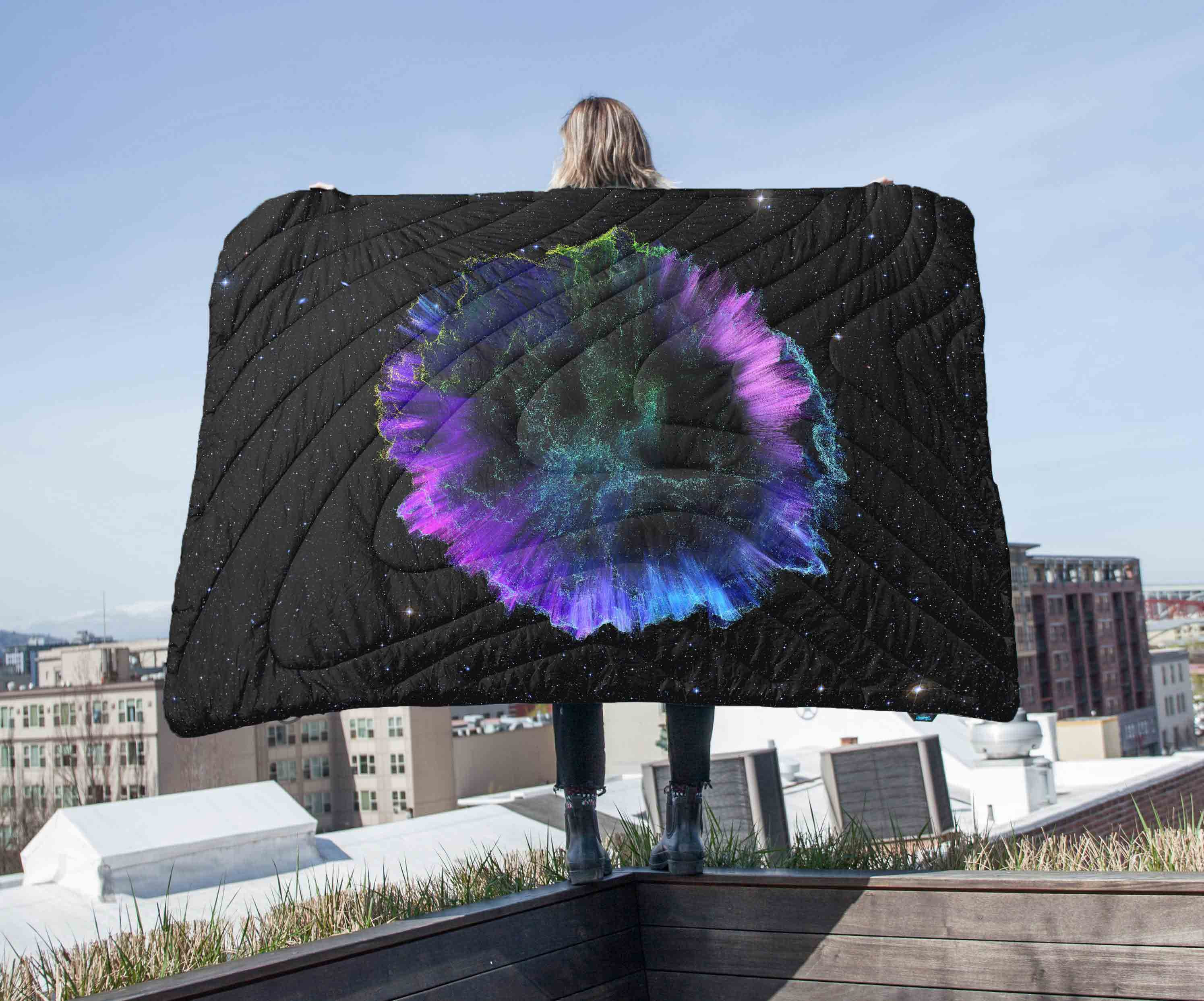Standing on a balcony holding up the Rumpl x Ion Sounds Original Puffy Blanket