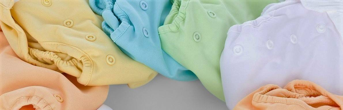 A collection of reusable nappies in a variety of pastel colours