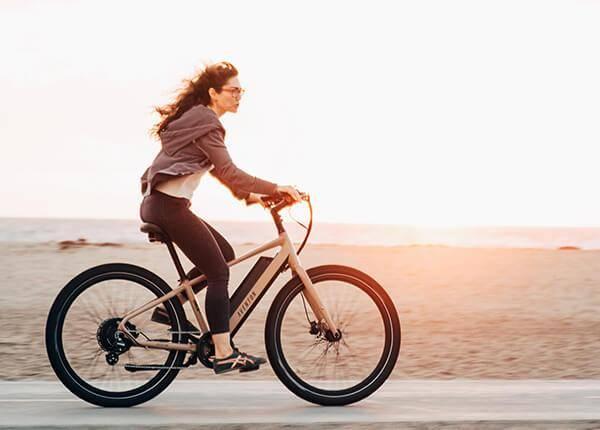 woman rides bike on path next to beach