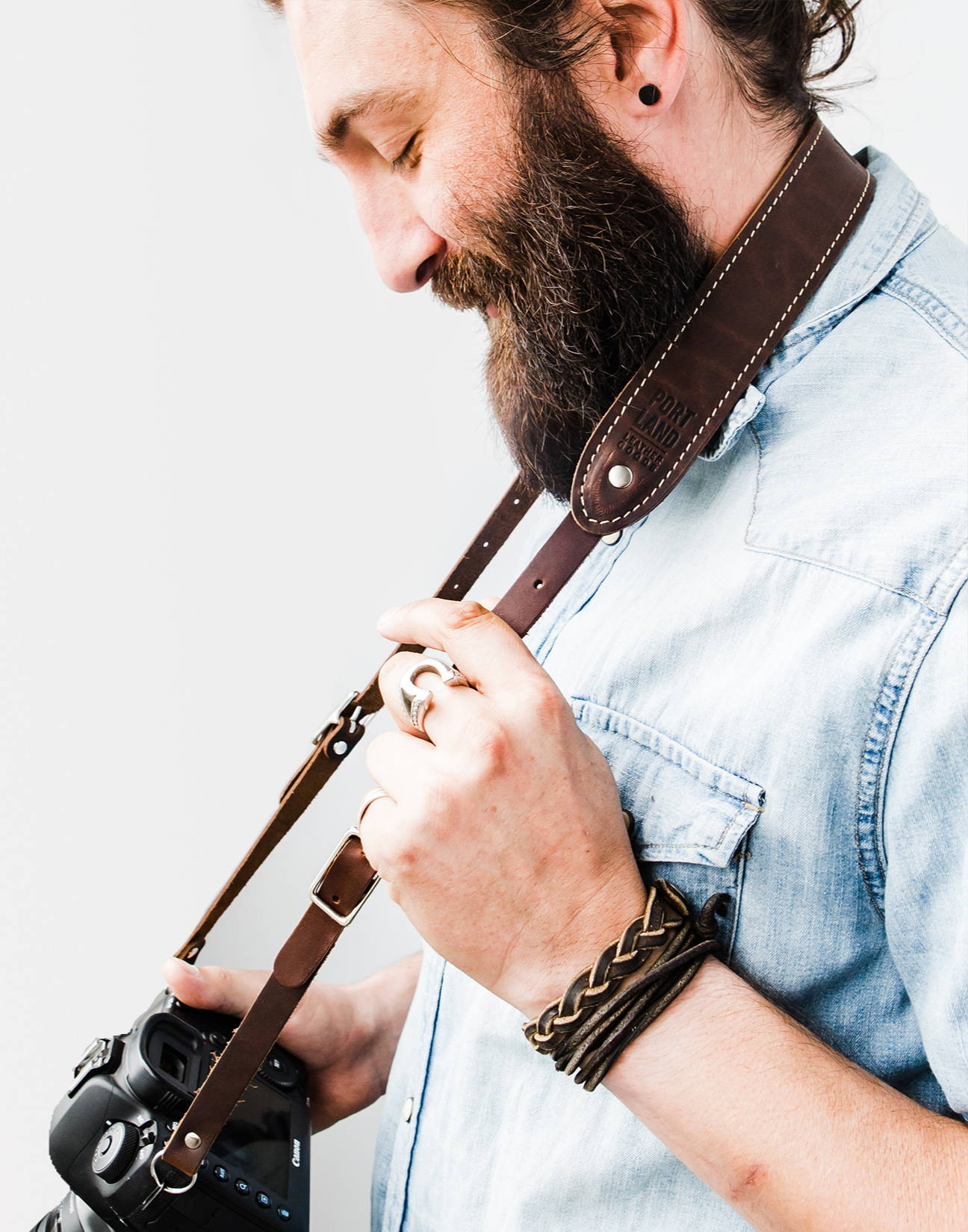 smiling handsome bearded man with a handmade leather camera strap around his neck