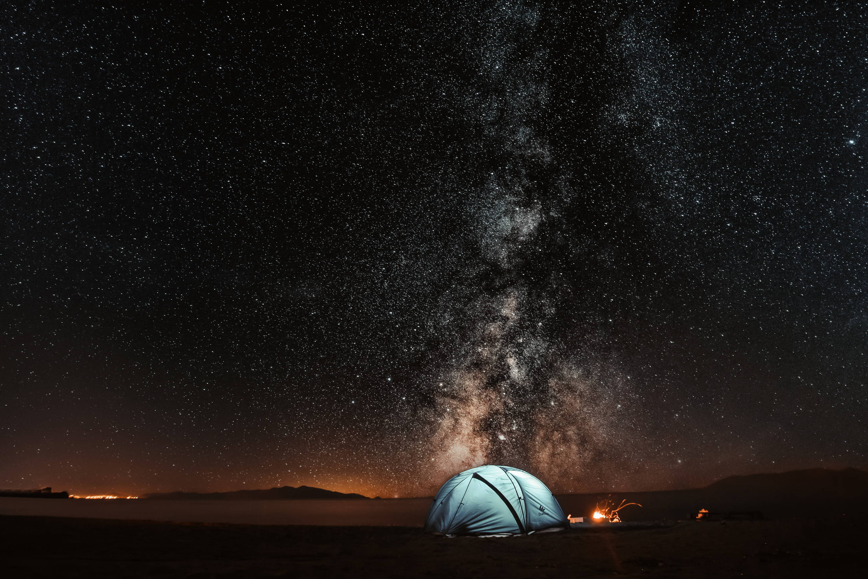 Backpacking Checklist: Essential Items for Adventure. Blue tent with light shining inside and campfire next to it sits under the brilliant night sky.