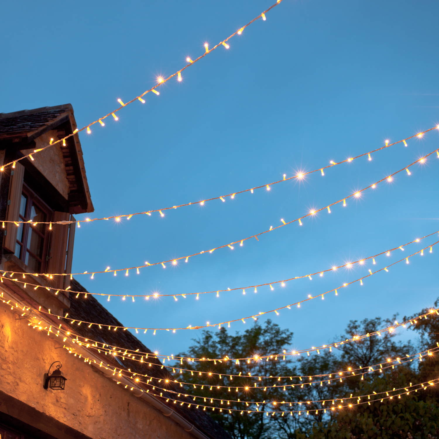 A canopy of warm white fairy lights in a blue sky