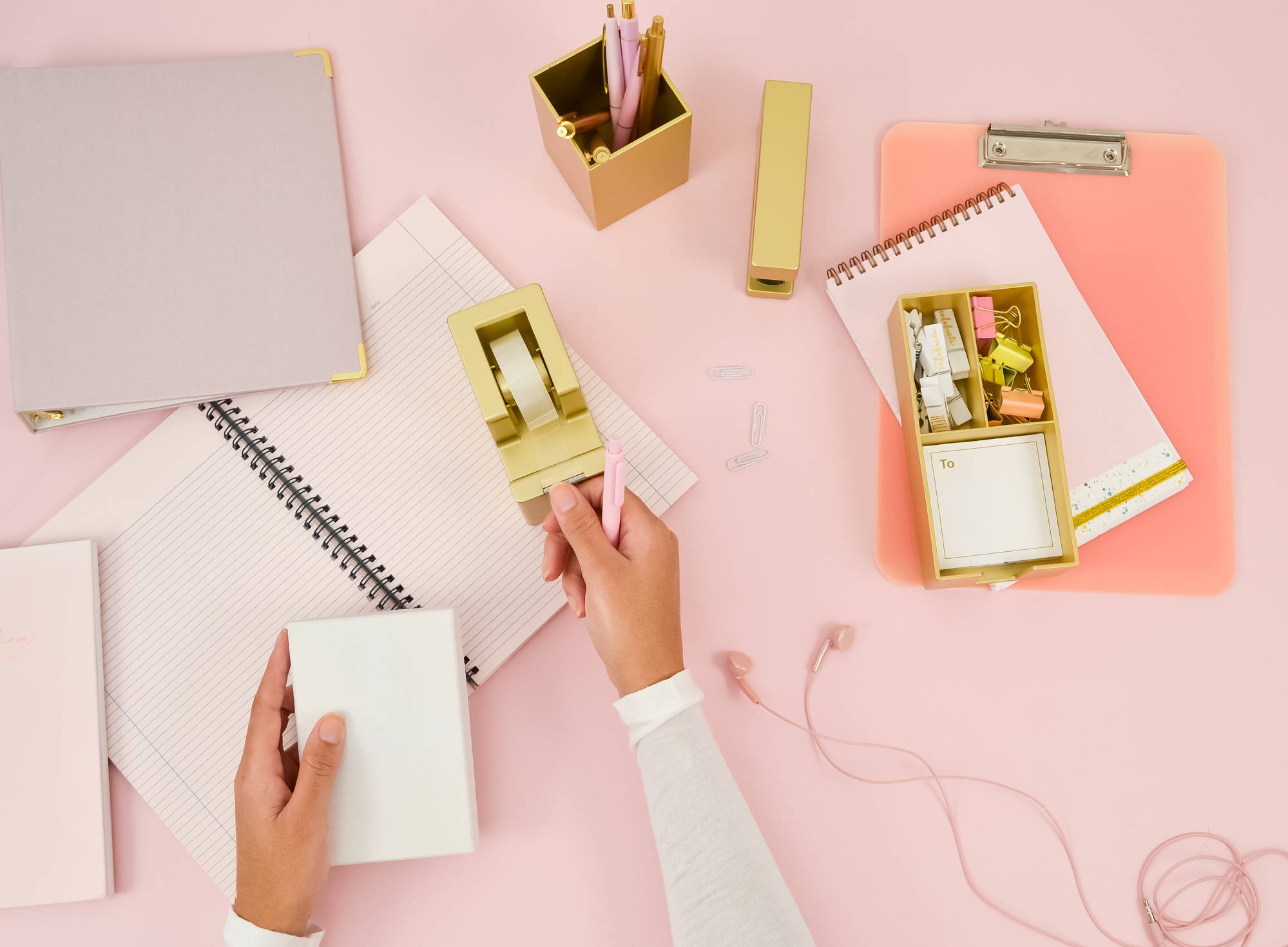 a cute flatlay of a gold desk set, headphones, and a taskpad