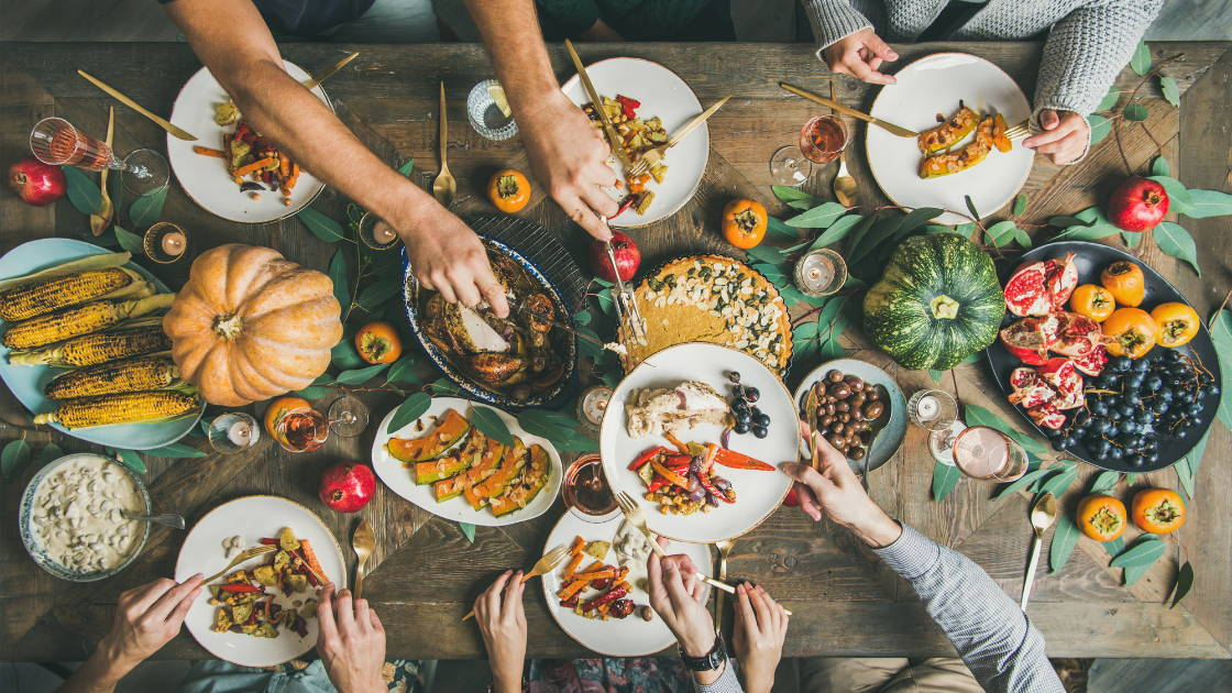 A Thanksgiving meal table filled with dishes and healthy vegetables