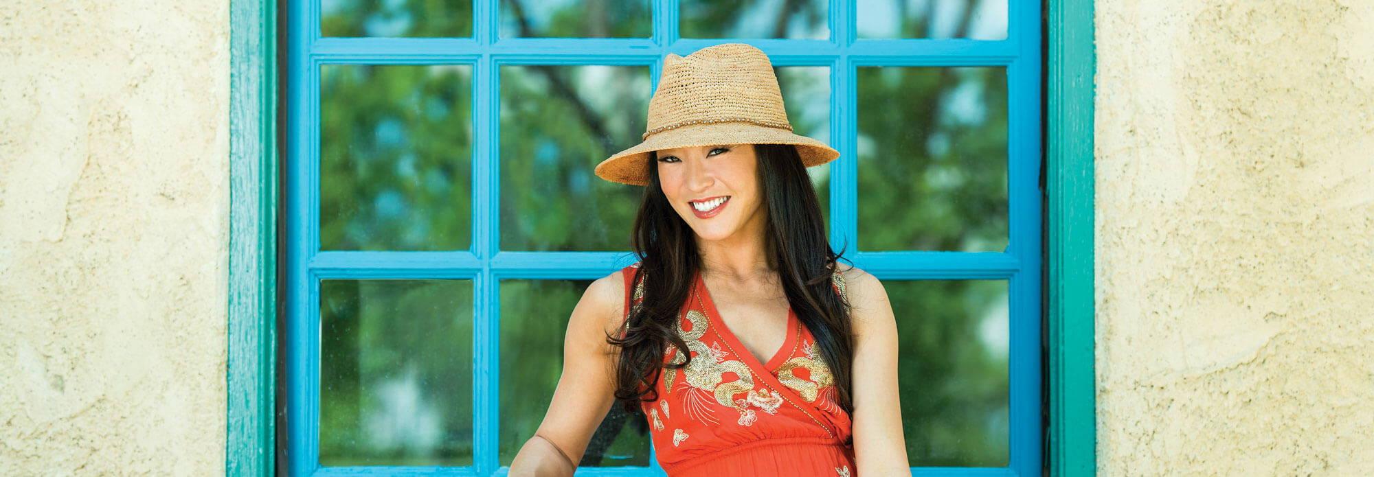 Asian woman wearing sun hat smiling