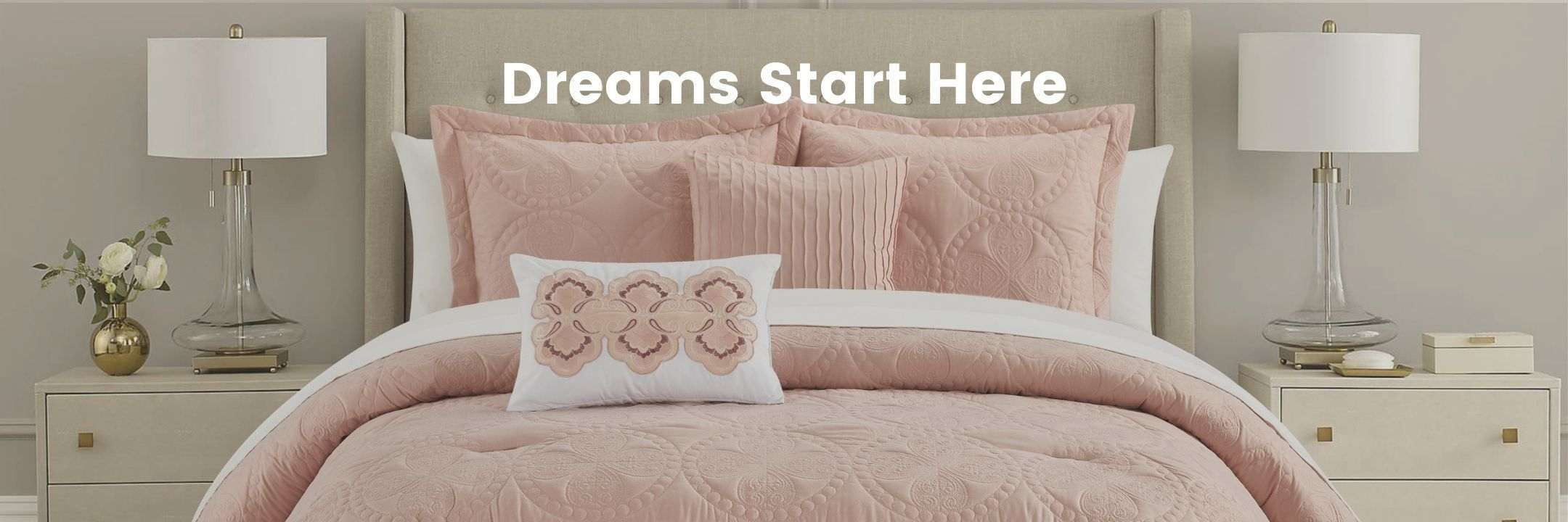 A bed with a blush comforter set on top of it