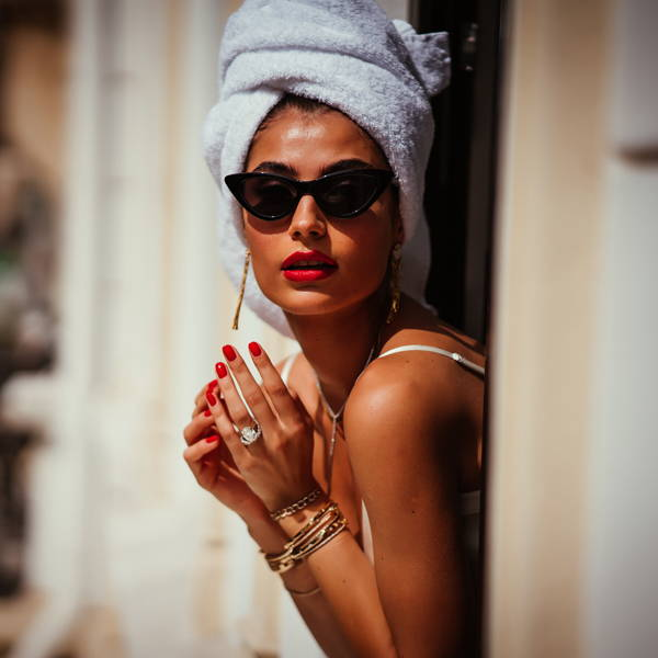 Model leaning out a window wearing Ring Concierge fine jewelry.