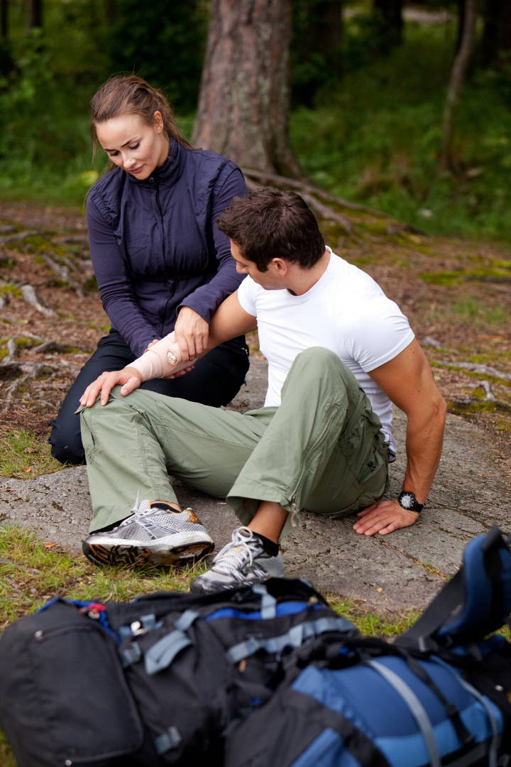 Woman wraps mans arm using first aid kits for hiking supplies