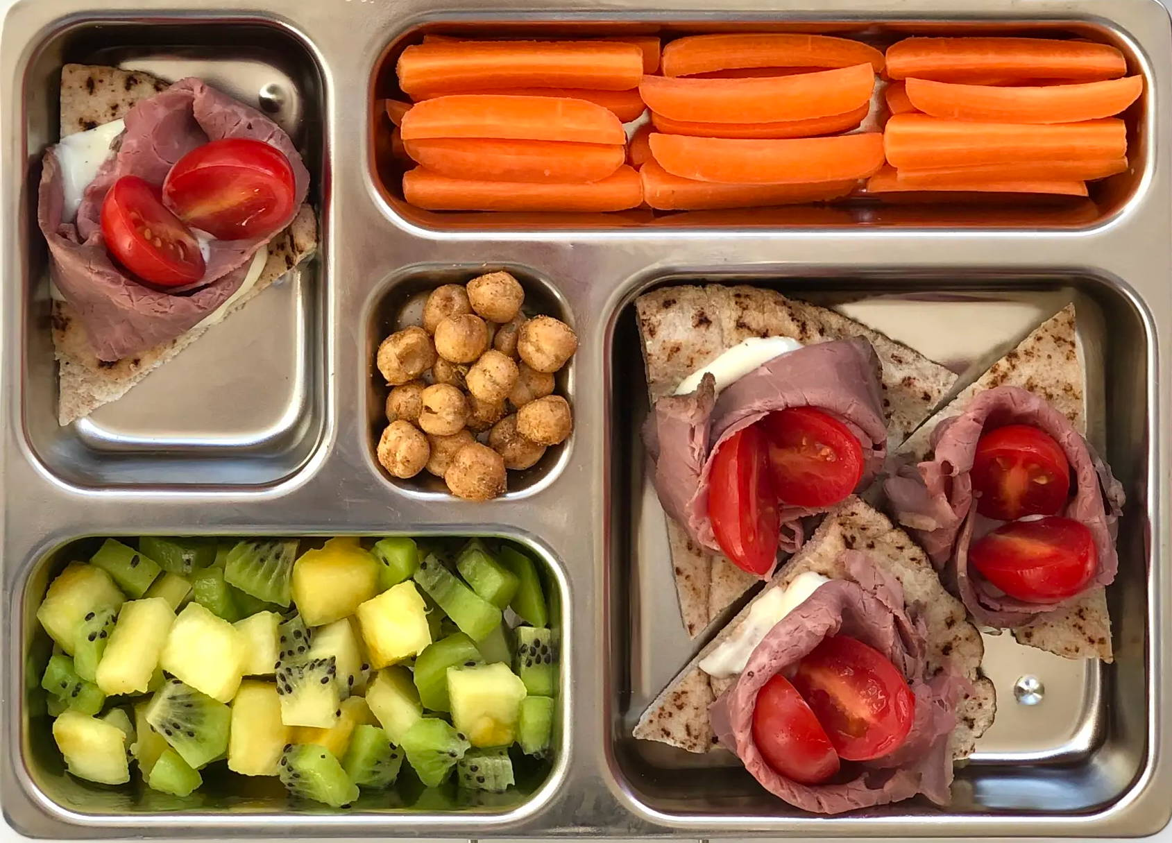 "Sneak peek of a kid's quick and healthy school lunch containing  Roast Beef Pita ""Crostini"" Wedges  Fresh Carrots Sticks,  Kiwi & Pineapple Fruit Salad,  and Flavored Roasted Chickpeas."