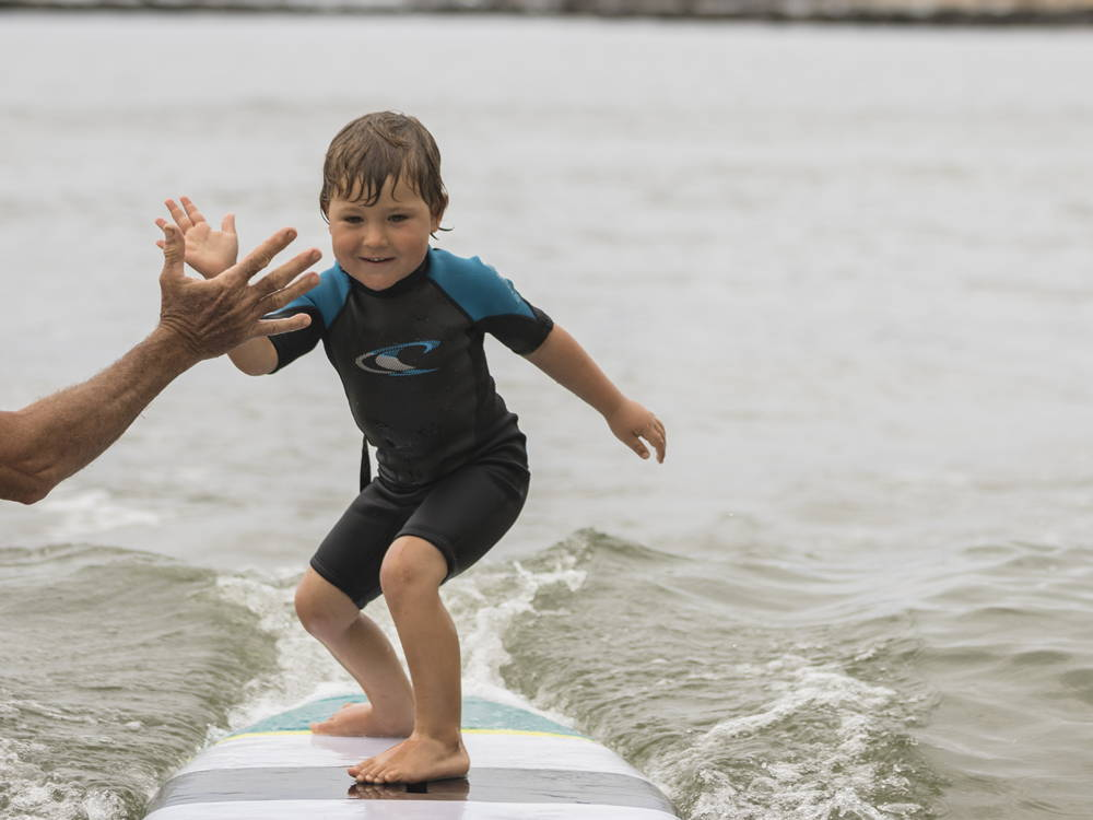 Kid high fiving while surfing the Grom SUP