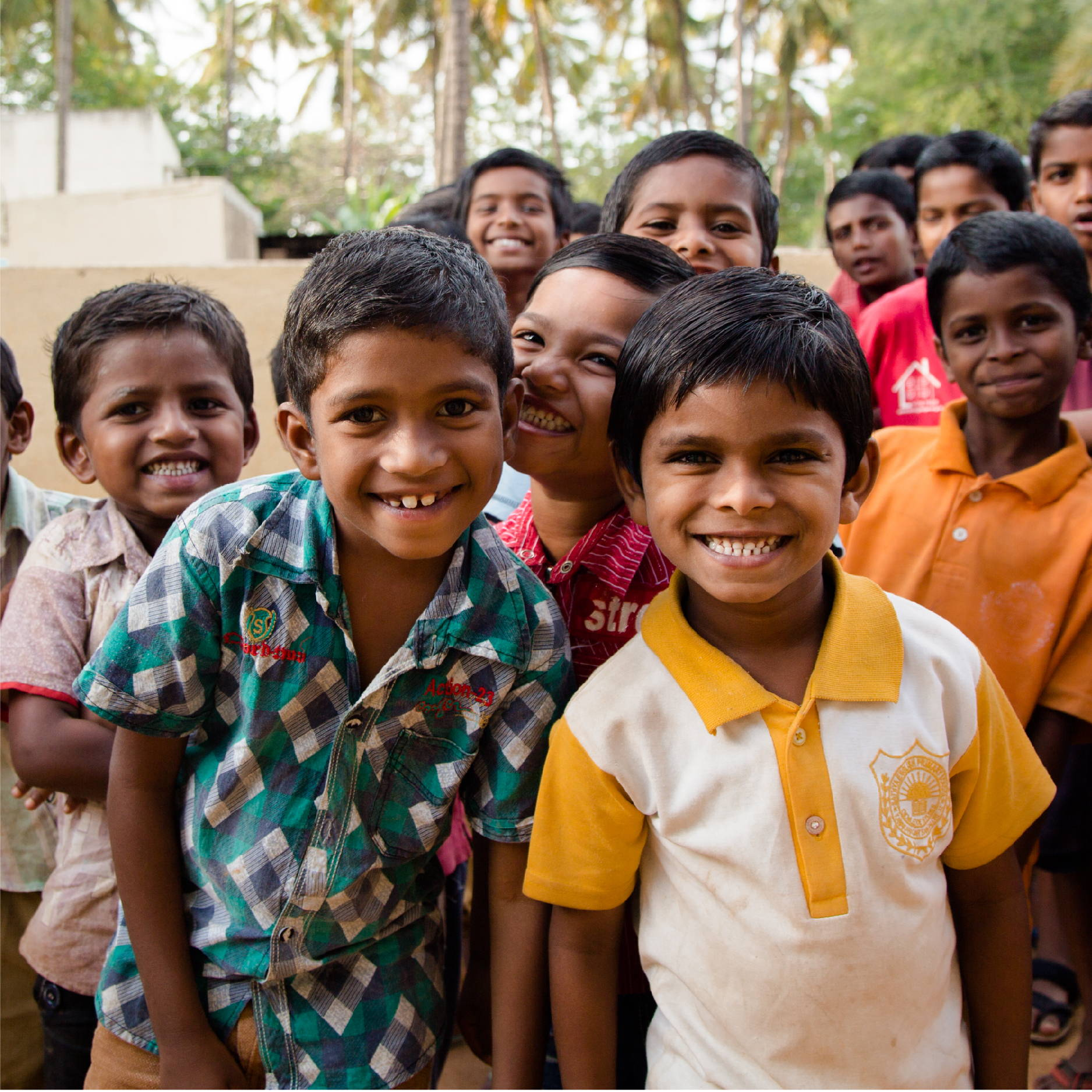 a large group of young Indian boys, around the age of 10, pose smiling and looking tough.