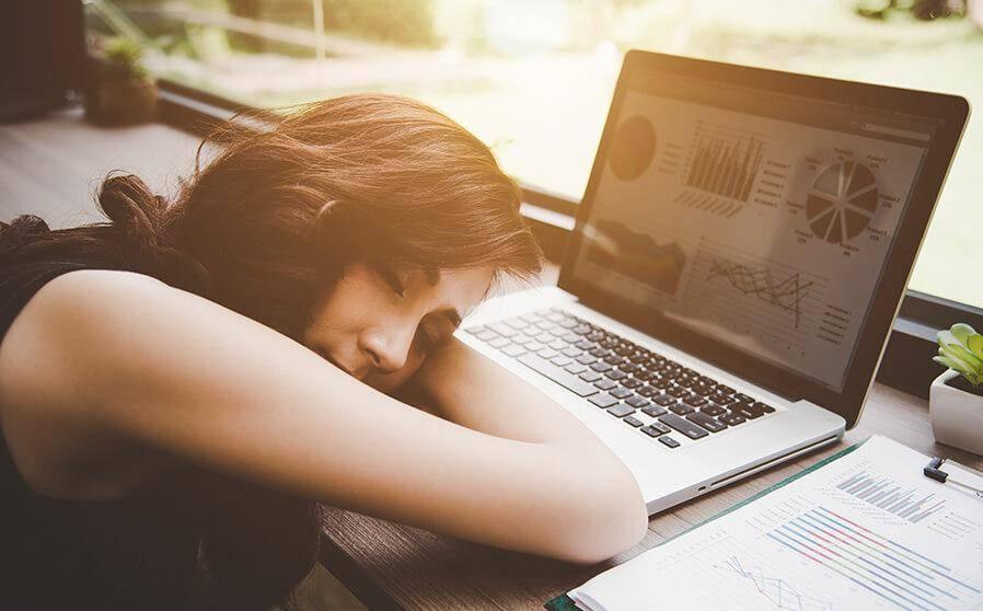 Frau macht Mittagsschlaf über Laptop