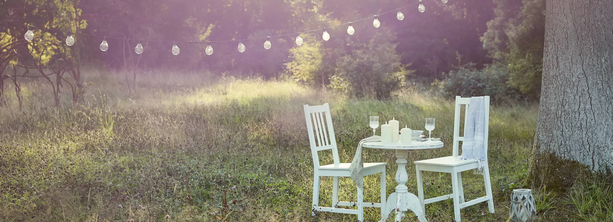 Summer dining setting with festoons draped over seating area with TruGlow candles displayed on table
