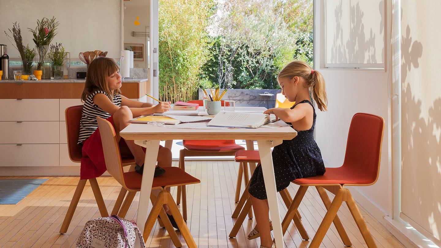 Two children doing homework at a Floyd dining table