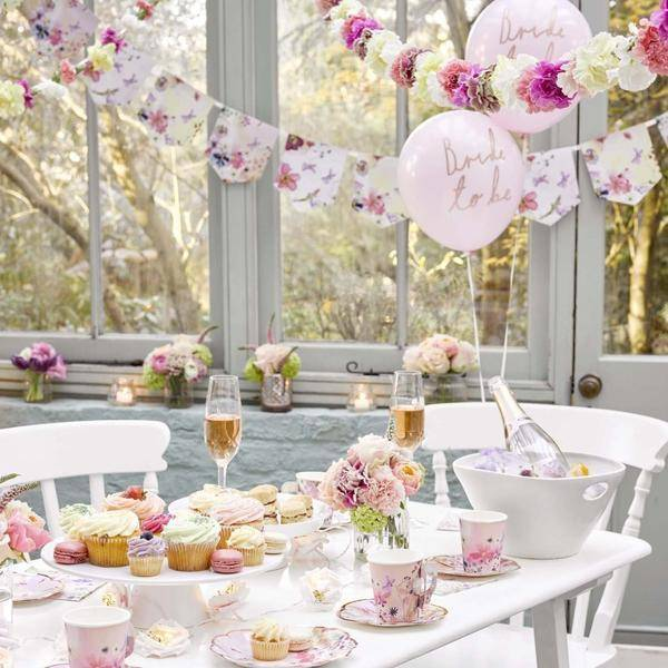 A beautifully decorated hen party table set up with sparkling wine and party cups in delicate floral designs with classy floral bunting and flowers for the hen party, along with pink balloons saying 'bride to be'
