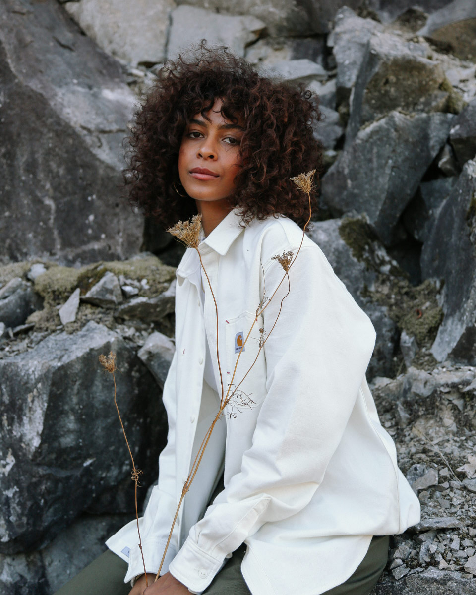 Woman with curly brown hair wearing a white, Carhartt brand long sleeve sitting on rocks.