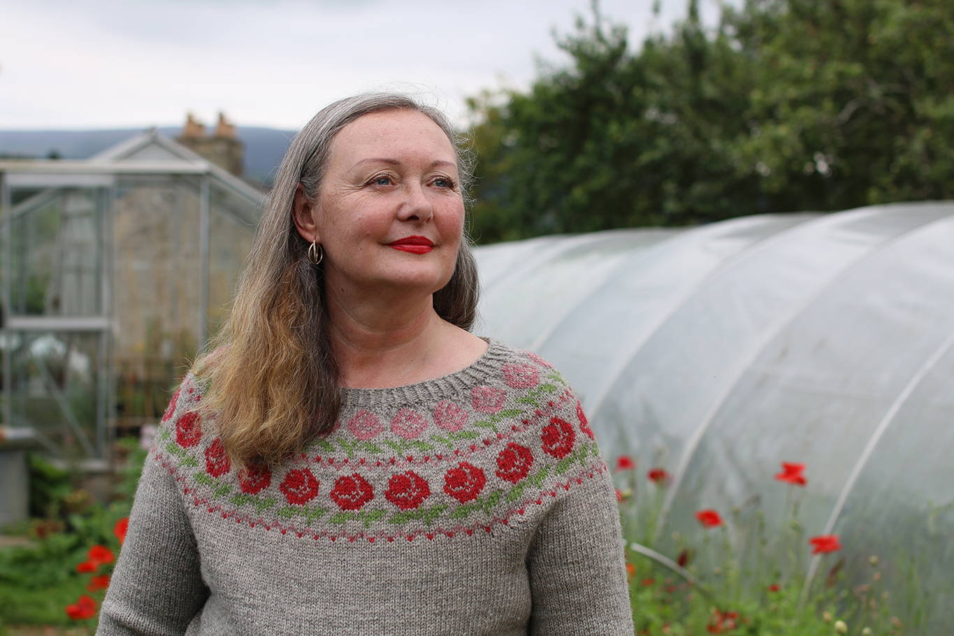 A woman wearing a grey sweater with a decorative yoke looking away from the camera with a green house and poly tunnel behind her