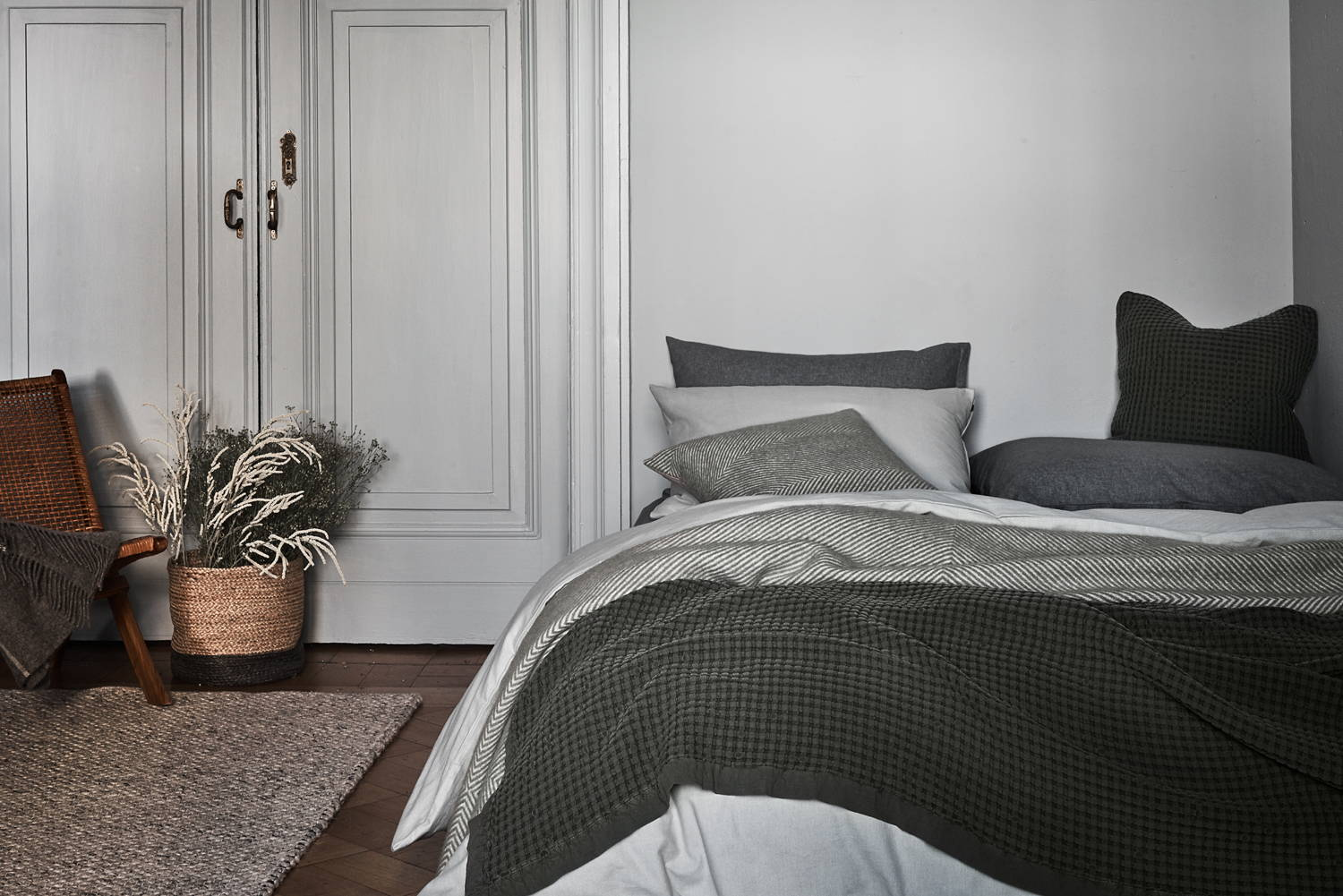 Lagom style bedroom with grey bed throws and grey and white bedding, jute basket and rattan chair