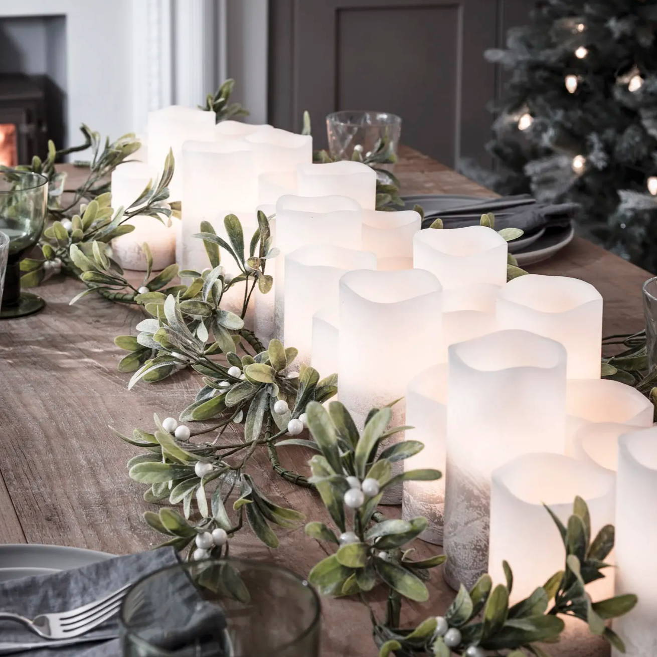 Christmas table setting lined with LED candles and a festive garland