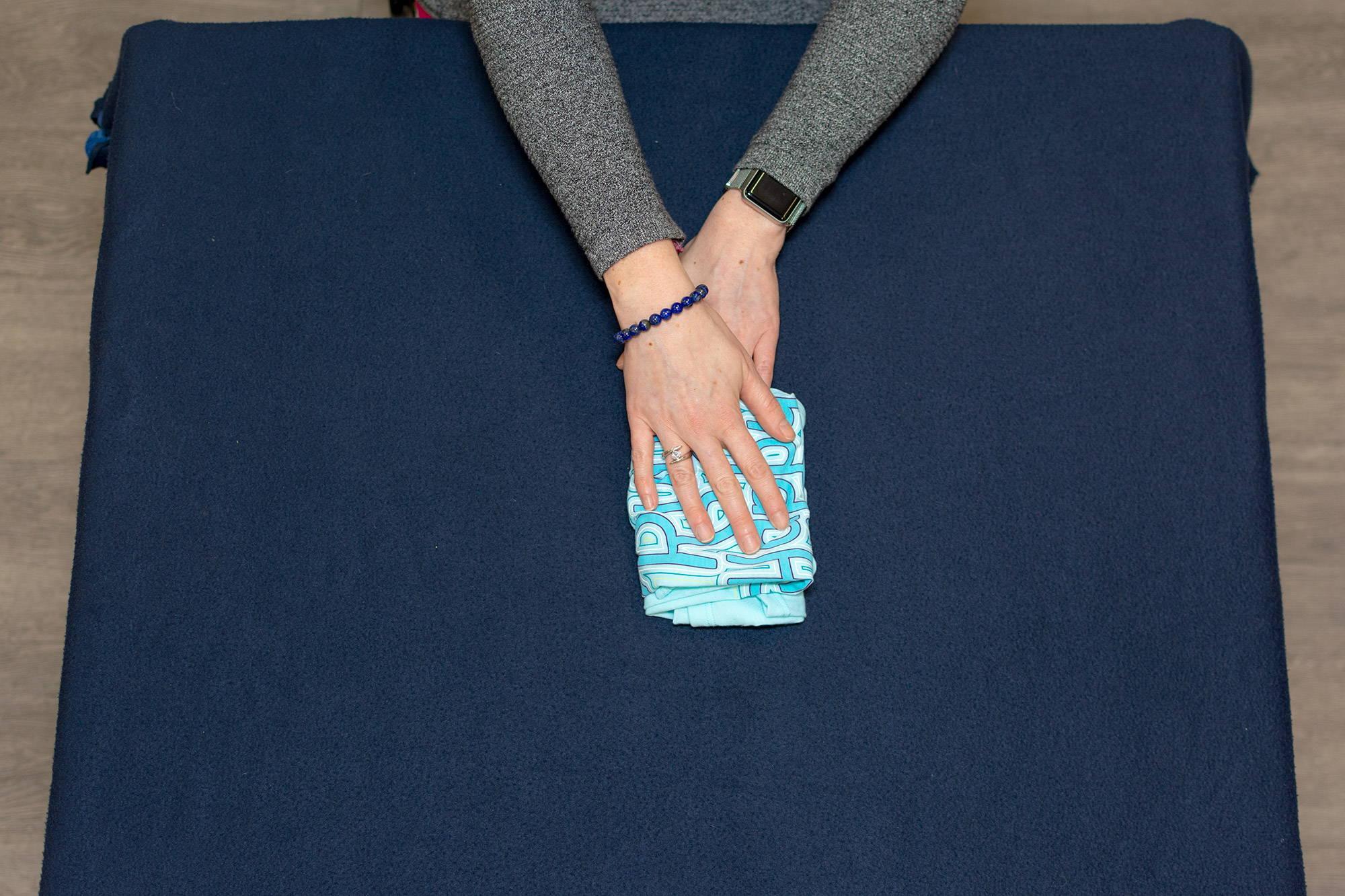 hands folding tank top