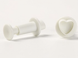 press stamps to create love hearts in polymer clay