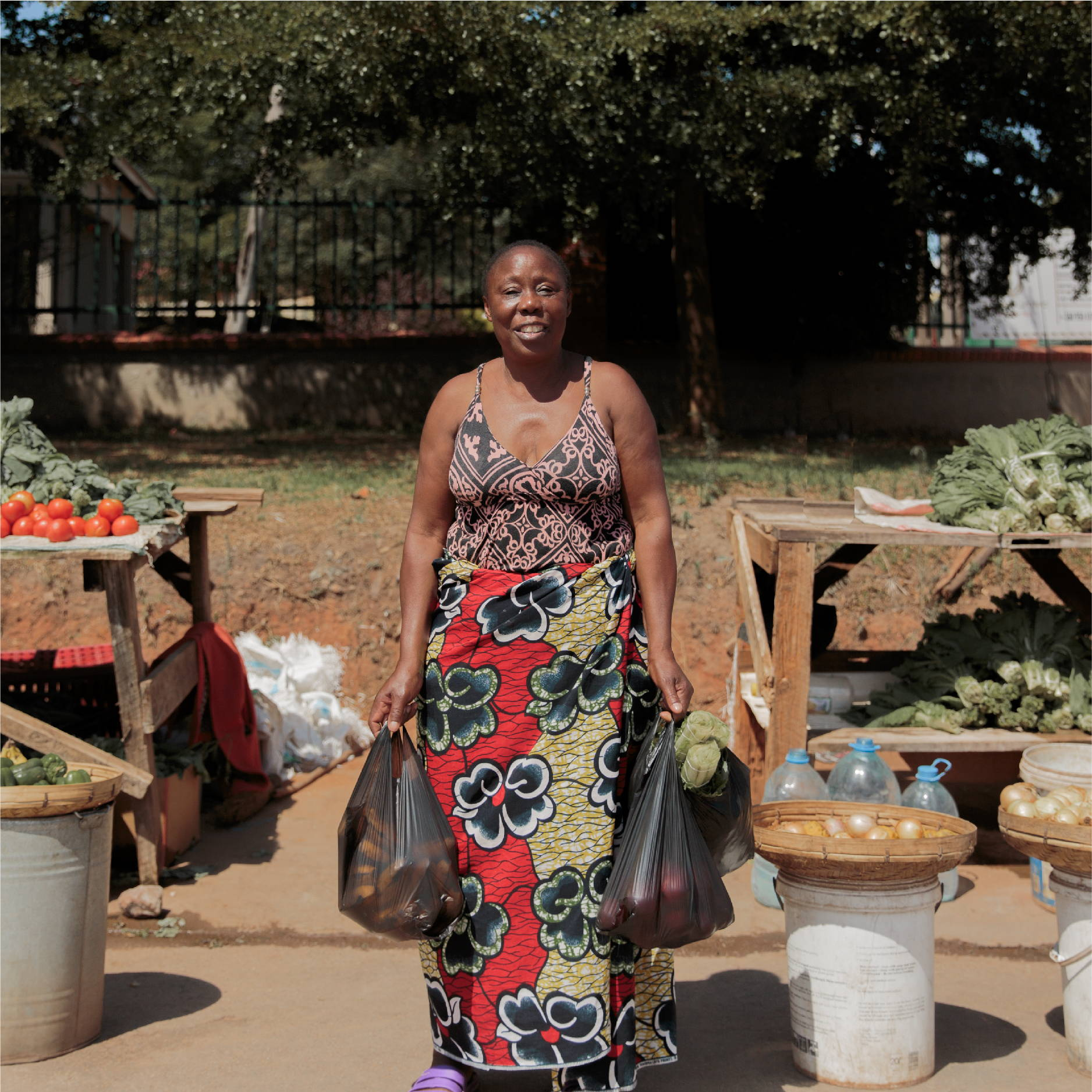 A woman stands smiling in front of two street vendors selling fresh local produce in Zambia. She holds two full black bags.