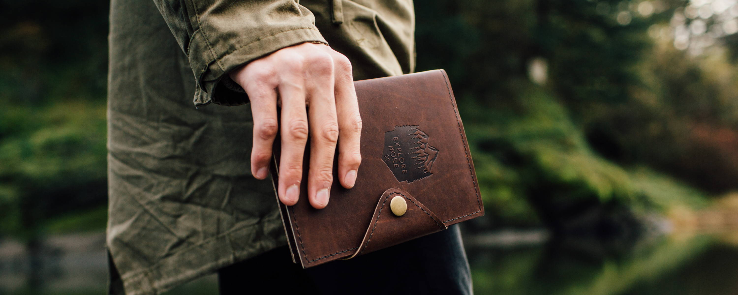 mans hand holding leather snap journal in forest scene