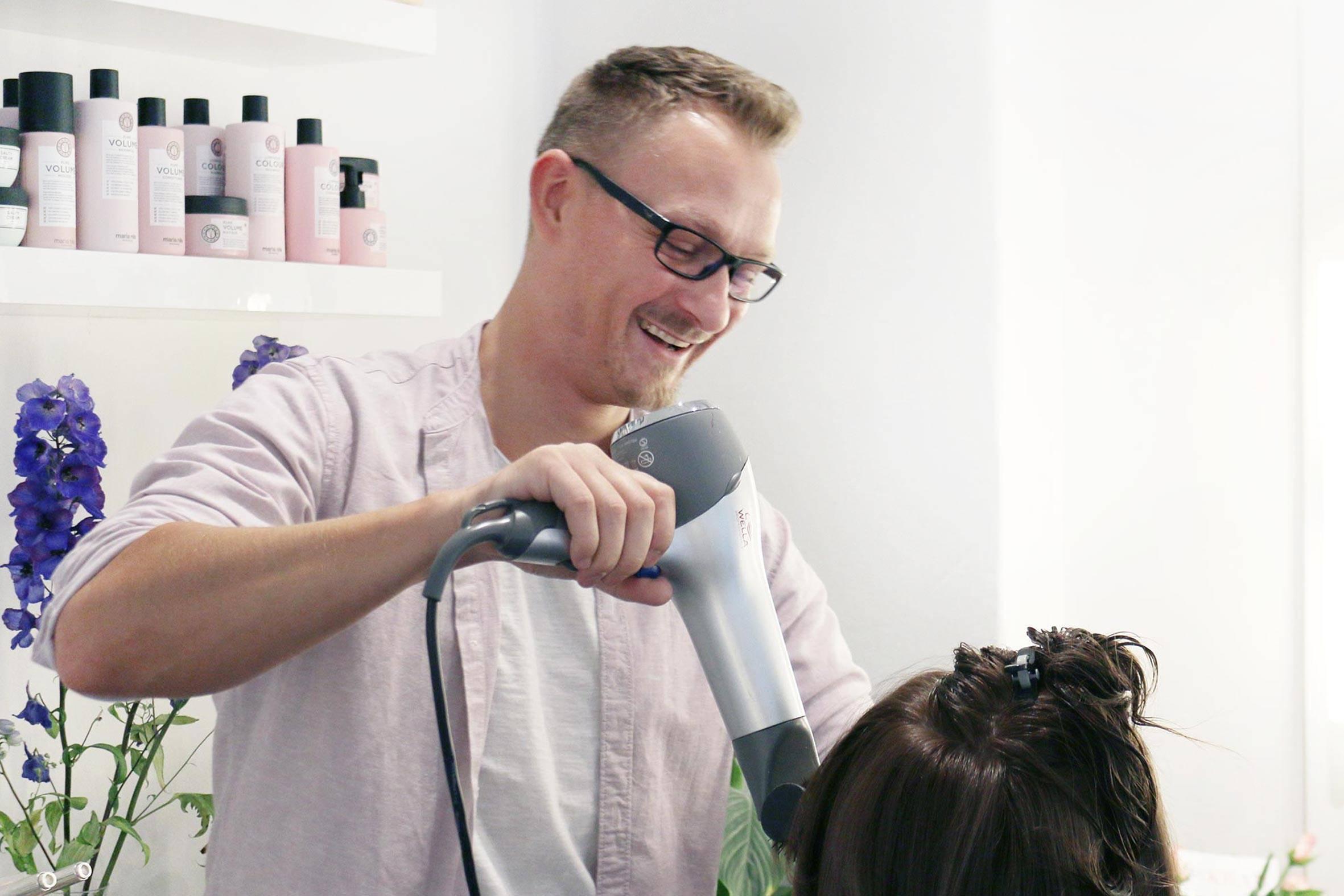 Friseurmeister Romano Klemd von PÜPPIKRAM föhnt einer Kundin die Haare